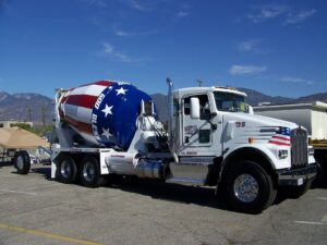 Concrete mixing truck with red white and blue drum